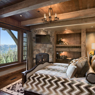 Bedroom - rustic guest dark wood floor bedroom idea in Other with beige walls, a corner fireplace and a stone fireplace