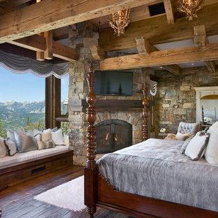 Modelo de dormitorio rural con suelo de madera oscura, chimenea de esquina y marco de chimenea de piedra