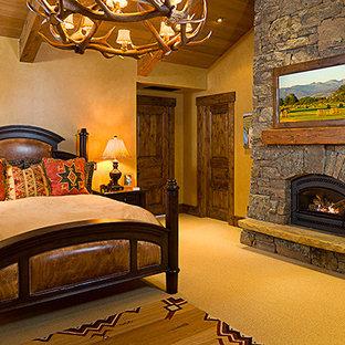 Ispirazione per una grande camera matrimoniale rustica con pareti beige, moquette, camino classico e cornice del camino in pietra