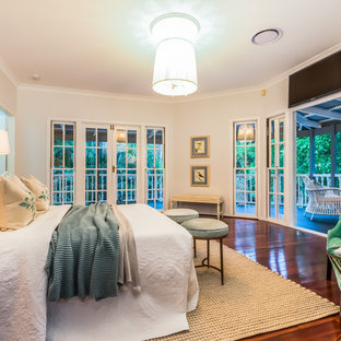 This is an example of a mid-sized beach style master bedroom in Brisbane with beige walls, dark hardwood floors and brown floor.
