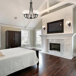 Пример оригинального дизайна: хозяйская спальня среднего размера в классическом стиле с бежевыми стенами, полом из фанеры, стандартным камином и фасадом камина из плитки