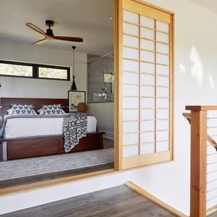 Idee per una piccola camera matrimoniale etnica con pareti bianche, pavimento in legno massello medio, camino ad angolo, cornice del camino in intonaco e pavimento marrone