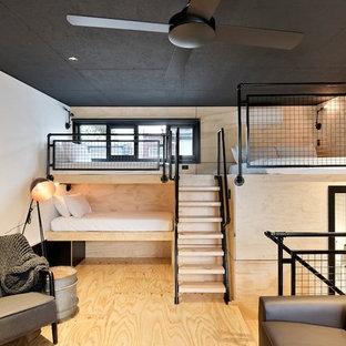 Ejemplo de dormitorio tipo loft, industrial, pequeño, con suelo de contrachapado