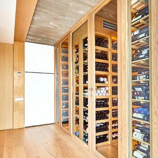 Foto de bodega actual, grande, con suelo de madera clara, botelleros y suelo beige