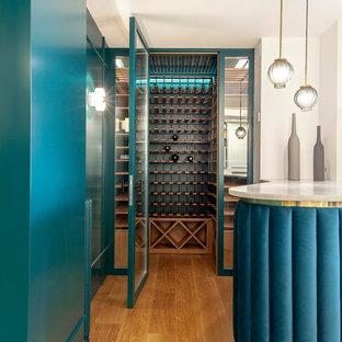 Imagen de bodega contemporánea con suelo de madera en tonos medios y botelleros