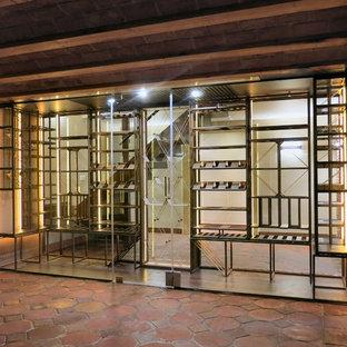 Imagen de bodega moderna, de tamaño medio, con suelo de baldosas de terracota y vitrinas expositoras