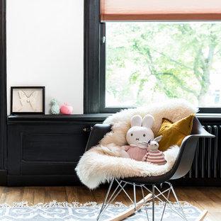 Cette image montre une chambre d'enfant de 1 à 3 ans nordique de taille moyenne avec un mur orange et un sol en bois brun.