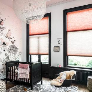 Cette photo montre une chambre d'enfant de 1 à 3 ans scandinave de taille moyenne avec un mur orange et un sol en bois brun.