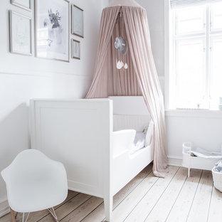 Inspiration pour une chambre de fille nordique avec un mur blanc, un sol en bois clair et un sol beige.