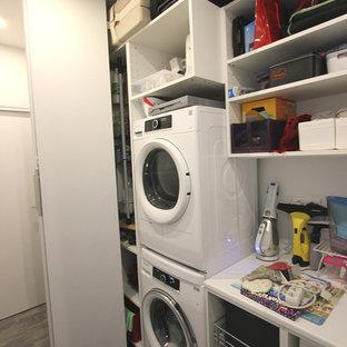 Immagine di una lavanderia multiuso contemporanea di medie dimensioni con ante lisce, ante bianche, top in laminato, pareti bianche, pavimento in laminato, lavatrice e asciugatrice a colonna, pavimento grigio e top bianco
