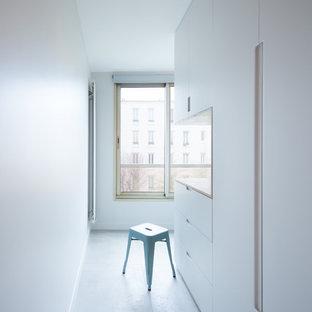 Esempio di una lavanderia multiuso scandinava di medie dimensioni con ante a filo, ante grigie, pavimento in cemento e top marrone