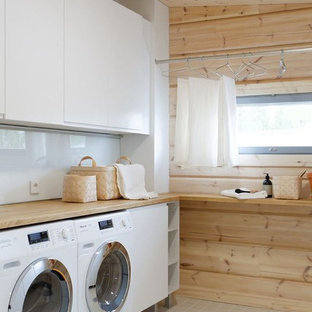 Inspiration for a mid-sized scandinavian single-wall utility room in Bordeaux with flat-panel cabinets, white cabinets, wood benchtops, beige walls, ceramic floors, a side-by-side washer and dryer and beige benchtop.