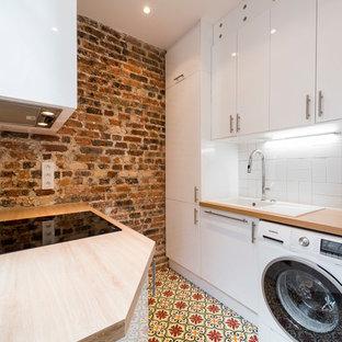 Exemple d'une buanderie méditerranéenne multi-usage avec un évier posé, un placard à porte plane, des portes de placard blanches, un plan de travail en bois, un mur rouge et un sol multicolore.