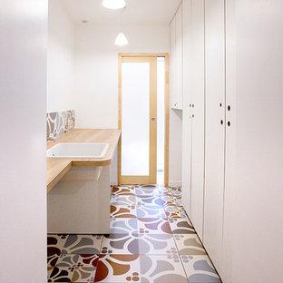 Idée de décoration pour une petite buanderie parallèle vintage dédiée avec un évier encastré, un placard à porte plane, des portes de placard blanches, un plan de travail en stratifié, un mur blanc et un sol en carrelage de céramique.