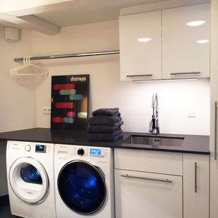Idéer för mellanstora funkis svart tvättstugor enbart för tvätt, med en enkel diskho, vita skåp, bänkskiva i kvartsit, vita väggar, klinkergolv i porslin, en tvättmaskin och torktumlare bredvid varandra och släta luckor