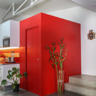 Bild på en liten industriell röda parallell rött tvättstuga enbart för tvätt, med luckor med infälld panel, röda skåp och bänkskiva i glas