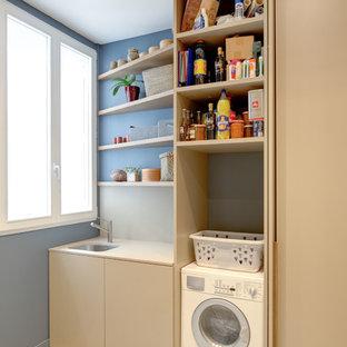 Idée de décoration pour une buanderie linéaire design multi-usage et de taille moyenne avec un évier encastré, des portes de placard beiges, un mur bleu et un sol en carrelage de céramique.