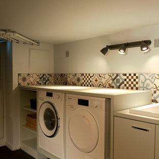 Idee per una grande lavanderia multiuso chic con lavello sottopiano, ante a filo, ante blu, top in saponaria, pareti multicolore, pavimento con piastrelle in ceramica, lavatrice e asciugatrice affiancate, pavimento nero e top blu
