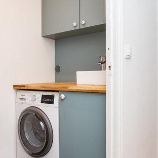 Foto di un piccolo ripostiglio-lavanderia nordico con lavello da incasso, ante lisce, ante grigie, top in legno, pareti bianche, pavimento con piastrelle in ceramica, lavasciuga, pavimento grigio e top marrone