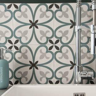 Exempel på ett stort industriellt grå grått grovkök, med en enkel diskho, kaklad bänkskiva, gröna väggar, klinkergolv i keramik, en tvättmaskin och torktumlare bredvid varandra och grått golv