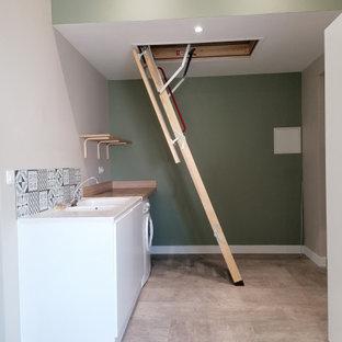 Idéer för att renovera ett stort minimalistiskt beige parallellt beige grovkök, med en undermonterad diskho, luckor med profilerade fronter, vita skåp, träbänkskiva, blått stänkskydd, stänkskydd i cementkakel, gröna väggar, en tvättmaskin och torktumlare bredvid varandra och beiget golv