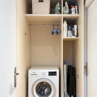 Foto på en liten funkis linjär liten tvättstuga med garderob, med släta luckor, vita skåp, vita väggar, ljust trägolv och beiget golv