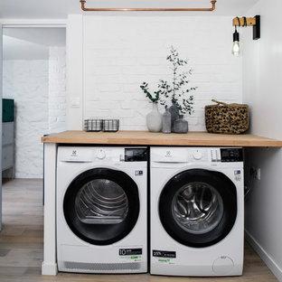 Ejemplo de cuarto de lavado escandinavo, grande, con encimera de madera, paredes blancas, suelo de madera clara y lavadora y secadora juntas