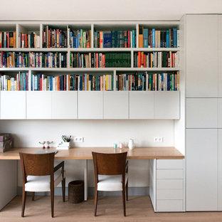 Cette image montre un grand bureau nordique avec un mur blanc, un sol en bois clair et un bureau intégré.