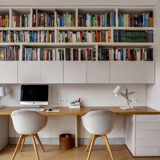 Cette photo montre un bureau scandinave avec un mur blanc, un sol en bois brun, un bureau intégré et un sol marron.