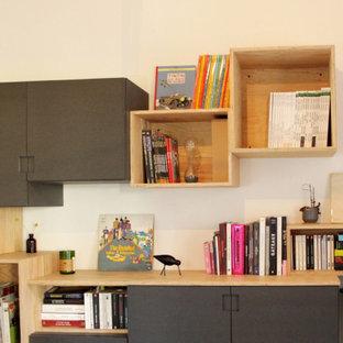 Modern inredning av ett mellanstort arbetsrum, med ett bibliotek, vita väggar, mörkt trägolv, en öppen hörnspis, en spiselkrans i gips, ett fristående skrivbord och brunt golv