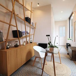 Стильный дизайн: рабочее место среднего размера в современном стиле с розовыми стенами, полом из терракотовой плитки, отдельно стоящим рабочим столом и синим полом - последний тренд