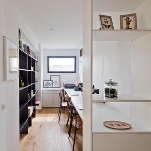 Cette image montre un bureau design de taille moyenne avec un sol en bois clair, un bureau intégré, un mur blanc et un sol marron.
