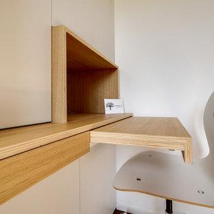 Idee per uno studio minimal di medie dimensioni con pareti bianche, pavimento con piastrelle in ceramica e scrivania incassata