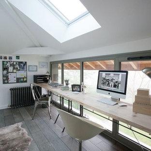Aménagement d'un bureau industriel de taille moyenne avec un mur blanc, un sol en bois clair, aucune cheminée, un bureau indépendant et un sol marron.