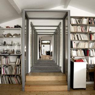 Cette photo montre un grand bureau industriel avec un mur blanc, un sol en bois clair et un bureau indépendant.