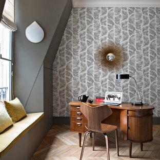 Cette photo montre un bureau chic avec un mur gris, un bureau indépendant, un sol marron et un sol en bois clair.