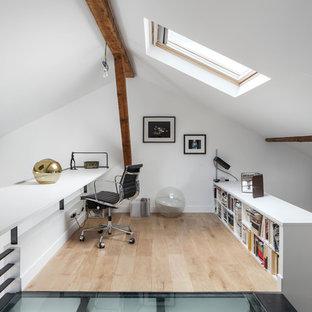 Cette photo montre un bureau tendance de taille moyenne avec un mur blanc, un sol en bois clair, un bureau intégré et aucune cheminée.