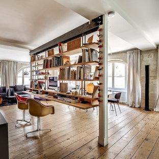 Cette image montre un grand bureau urbain avec un bureau intégré et un sol en bois brun.