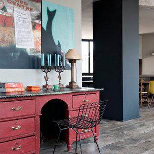 Industriell inredning av ett mellanstort hemmabibliotek, med grå väggar, mörkt trägolv och ett fristående skrivbord