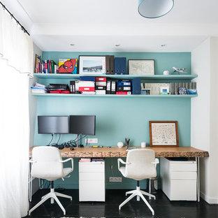 Ejemplo de despacho actual, de tamaño medio, con suelo de madera pintada, escritorio independiente, suelo negro y paredes blancas