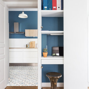 Study room - small scandinavian built-in desk medium tone wood floor study room idea in Paris with blue walls and no fireplace