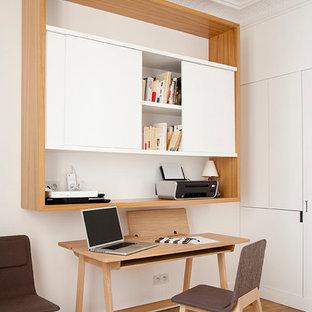 На фото: рабочее место в скандинавском стиле с белыми стенами, светлым паркетным полом и отдельно стоящим рабочим столом с