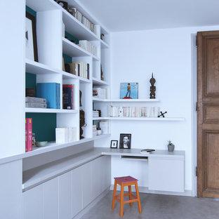 Réalisation d'un bureau design avec un mur blanc, béton au sol, aucune cheminée et un bureau intégré.