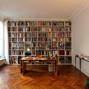 Bild på ett stort funkis hemmabibliotek, med mellanmörkt trägolv, ett fristående skrivbord och vita väggar