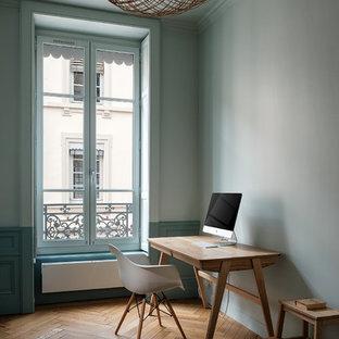 Cette image montre un bureau design avec un mur vert, un sol en bois brun, un bureau indépendant et un sol marron.