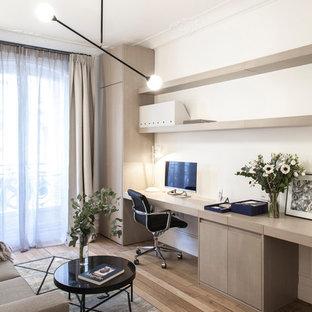 Réalisation d'un bureau nordique avec un mur blanc, un sol en bois clair, aucune cheminée et un bureau intégré.