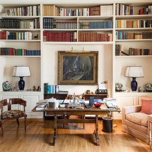 Ispirazione per uno studio tradizionale con libreria, pareti bianche, pavimento in legno massello medio, scrivania autoportante e pavimento marrone