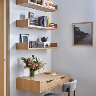 Foto di un ufficio minimal con pareti bianche, parquet chiaro e scrivania incassata