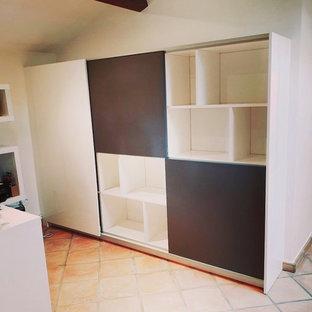 Cette image montre un petit bureau design avec un mur blanc, un sol en carreau de terre cuite, aucune cheminée, un bureau indépendant et un sol orange.