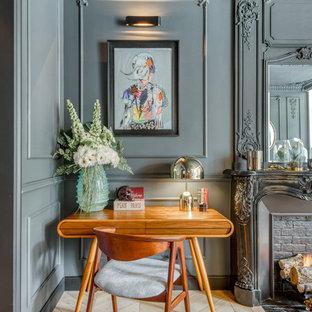 Ejemplo de despacho bohemio con paredes grises, suelo de madera clara, chimenea tradicional, marco de chimenea de ladrillo, escritorio independiente y suelo beige